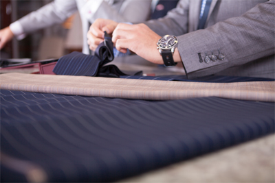 Tailor in the process of making a custom suit jacket for a business professional