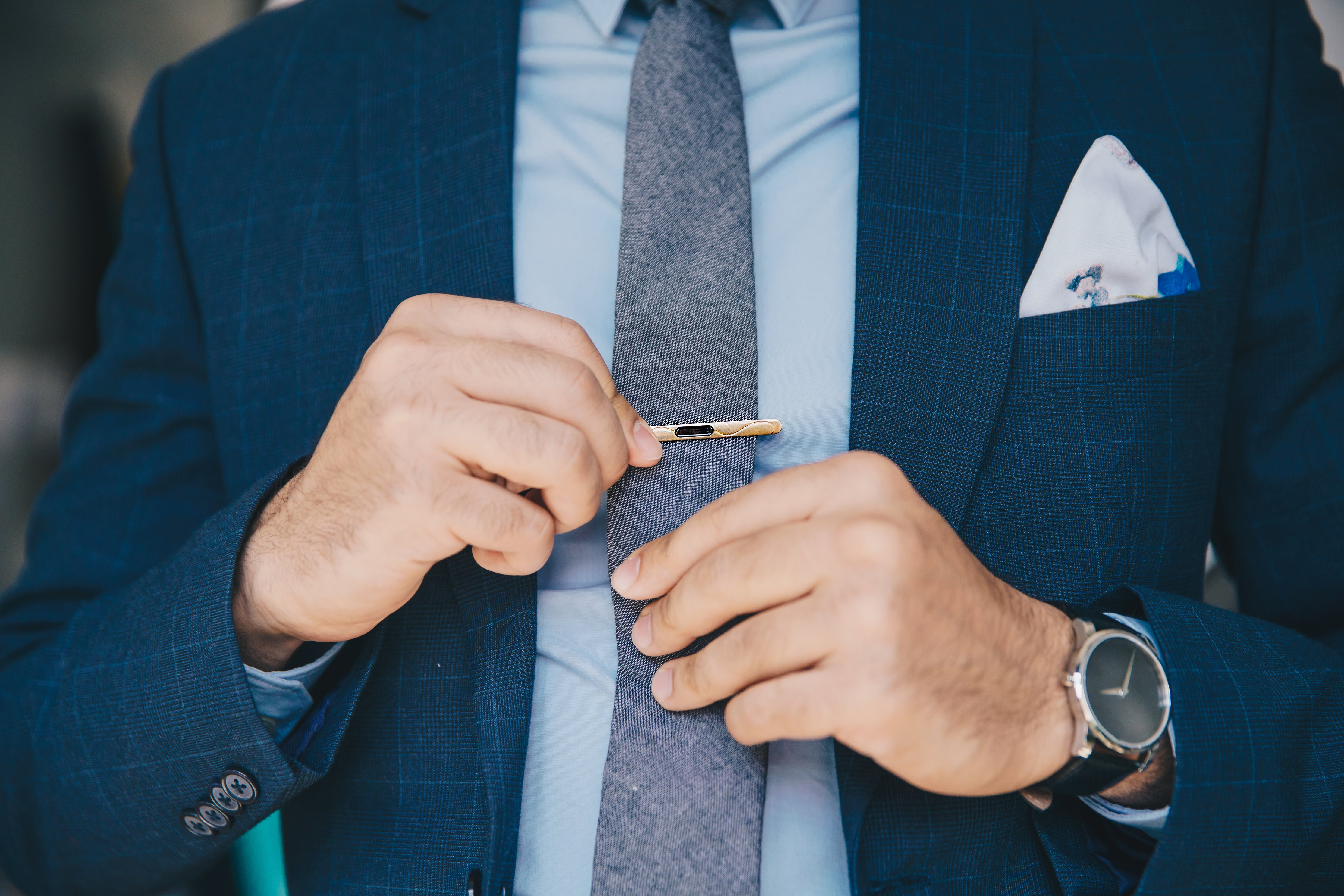 A man wearing his custom-made blue suit & clipping his tie with tie-pin.