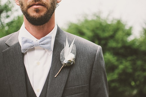 A man posing in his custom-made grey waistcoat &  custom-made grey suit in a wedding.